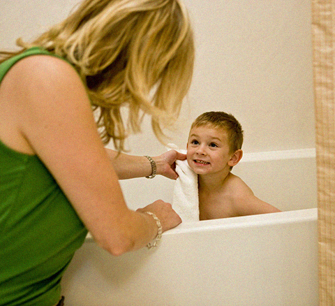 A young boy with his parent in the bathtub